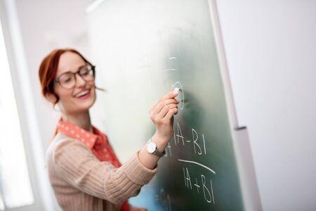 Writing on blackboard. Smiling pleasant teacher wearing glasses holding chalk while writing on blackboard