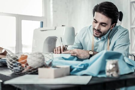 Just attention. Pleased young designer keeping smile on his face while using sewing-machine