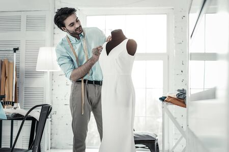 Good mood. Kind brunette man keeping smile on his face while looking at white dress Imagens