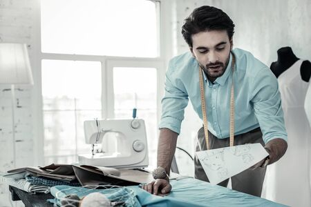 Real picture. Concentrated designer leaning on table while working at his fashion collection