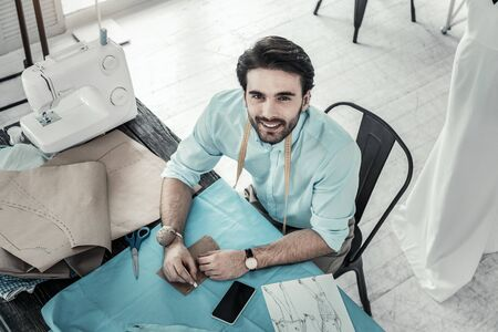 Follow me. Kind young male person keeping smile on his face while working with pleasure Banque d'images