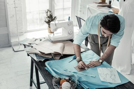 Making notes. Serious tailor bowing head while leaning on table Stock Photo