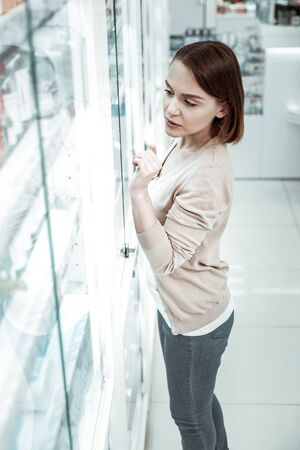 Hesitating over a choice. An attractive charming lady hesitating over a choice of pills in the huge drugstore.