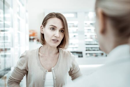 Pharmacist advice. A comely beautiful lady with a short haircut in her 30s asking for pharmacist s advice regarding her stomach ache problems.