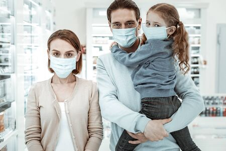Medical face mask. Concernedly looking family of three in the drugstore wearing a white medical face mask for the health protection.