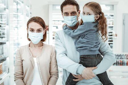 Medisch gezichtsmasker. Bezorgd uitziende familie van drie in de drogisterij met een wit medisch gezichtsmasker voor de bescherming van de gezondheid. Stockfoto