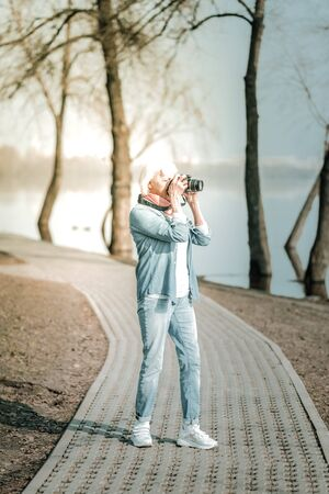 Taking pictures in the park. Stylish vigorous septuagenarian woman in denim blue clothes and short grey hair taking pictures in the park 免版税图像 - 130384270
