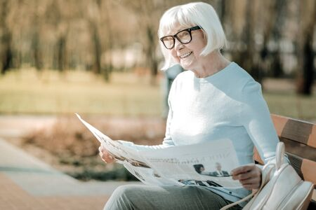 Reading news. Energetic cheerful well-flavored aging white-haired woman in glasses passionately reading news from the local paper with a smile on her face