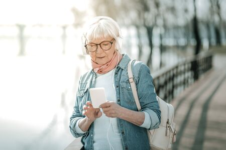 Elderly woman in headphones. Focused vigorous dame with silver short hair in massive white headsets and pink scarf holding a music player taking a walk in the park