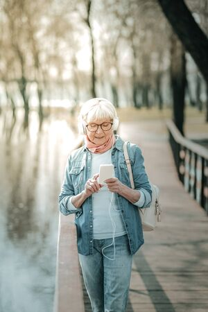 Aged dame in headsets. Concentrated elderly grey-haired missis in jeans clothing with a white backpack wearing headsets and glasses switching music on the player in the park