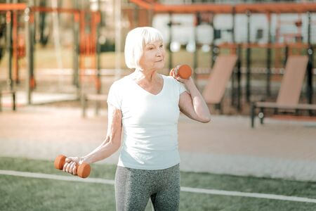 Sport for elderly. Sporty old happy looking lady wearing athletic apparel doing a physical workout for arms with weights outdoor. 免版税图像