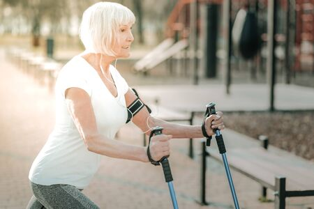 Physical activity outdoor. Active beauteous elderly woman wearing white t-shirt enjoying her daily exercises with walking poles outdoor.