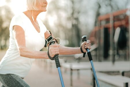 Workout with walking poles. Vigorous aged sporty lady with short grey hair working out with walking poles on the sportsground and listening to music with headsets