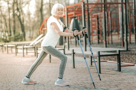 Long steps with walking poles. Appealing sporty madam in advanced years wearing workout clothing doing long steps with walking poles on the athletic ground