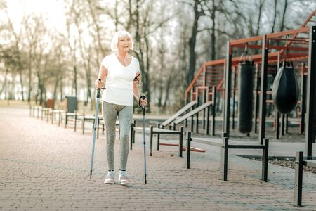 Nordic walking. Old-aged laughing pleasant woman in a good sporty shape doing Nordic walking on the sportsground.