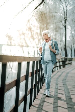 A walk in the park. Peaceful grey-haired woman wearing denim clothing in big white earphone with a phone walking down the bridge