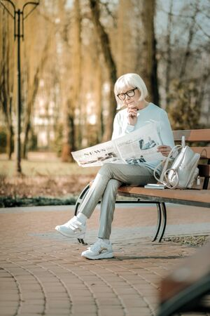 Reading in the park. Pleasant superannuated lady with short grey haircut in black glasses thoughtfully reading newspaper on the park bench