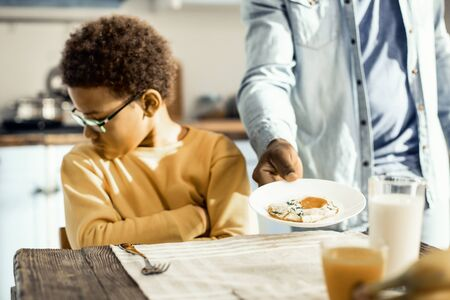 Offended kid. Impish boy in glasses does not want eggs for breakfast today, even though his dad insists.