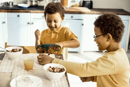 Kitchen quarrel. Sweet twins are trying to feed the toy with corn flakes during morning get-together. Stock Photo