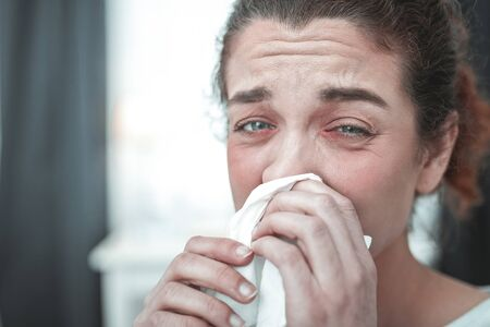 Laufende Nase. Grünäugige lockige reife Frau trocknet ihre laufende Nase nach starker Allergie drying Standard-Bild