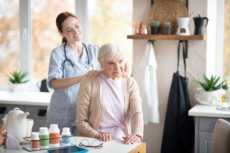 Doing some massage. Caregiver smiling while doing some shoulder massage for aged woman 版權商用圖片