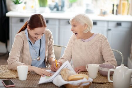 Laughing while reading. Caregiver and her patient laughing while reading news and having breakfast