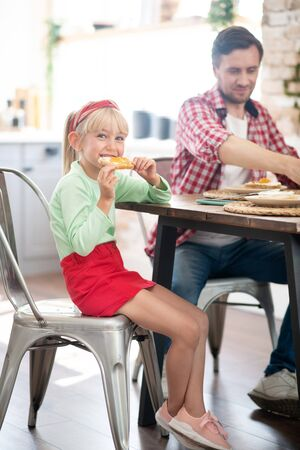 Daughter eating. Daughter wearing red skirt eating yummy toast for breakfast with father 写真素材