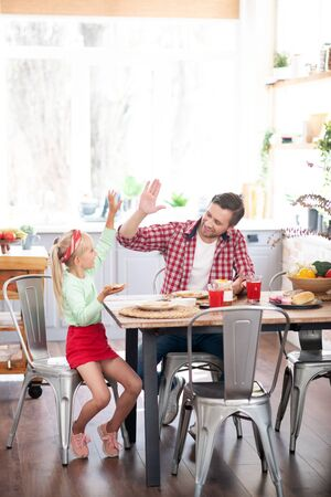High five. Cute lovely daughter giving high five to father while having yummy breakfast 写真素材 - 131688377