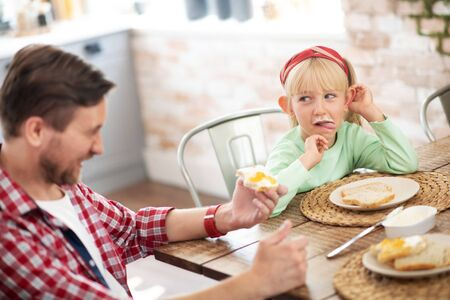 Father laughing. Father laughing while watching daughter eating eggs and toasts for breakfast 写真素材 - 131688433