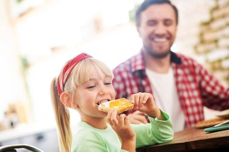 Toast with egg. Blonde-haired cute girl eating yummy toast with egg for breakfast 写真素材 - 131688640