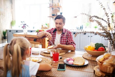 Father talking. Bearded loving father talking to his lovely girl while eating toasts for breakfast 写真素材 - 131688625
