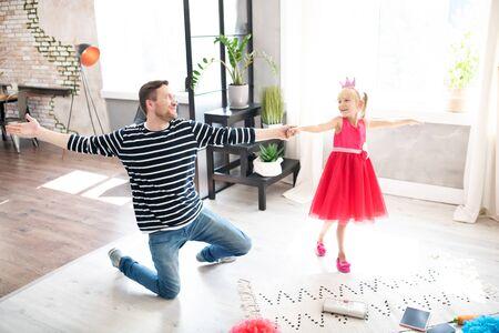 Lovely little princess. Businessman feeling happy while dancing with his lovely little princess