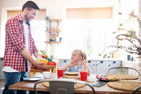 Bringing some vegetables. Loving daddy bringing some vegetables for breakfast while daughter eating