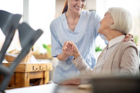 Thanking caregiver. Grey-haired aged woman thanking caregiver for help and support