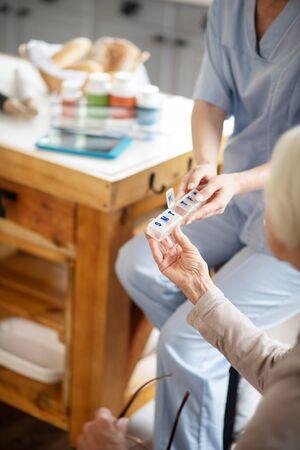 Nurse giving pills. Caring professional nurse wearing uniform giving pills to patient