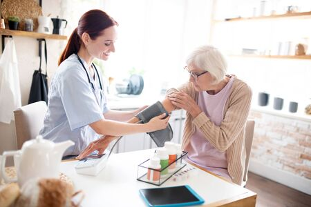 Nurse measuring pressure. Nurse measuring pressure for grey-haired pensioner before giving pills