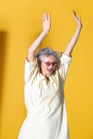 Woman feeling free. Mature woman feeling free and motivated while posing near yellow background