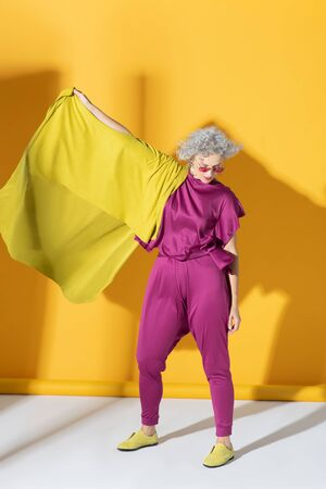 Mature model. Curly mature model wearing bright pink clothing posing near background Stock fotó