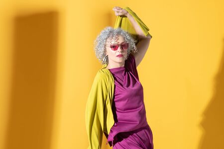 Wearing bright clothing. Beautiful curly mature woman wearing bright clothing and sunglasses
