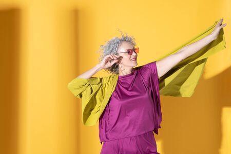 Woman posing. Woman wearing pink clothing having playful mood posing near background
