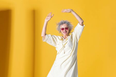 Moving and posing. Mature curly woman wearing bright sunglasses moving and posing