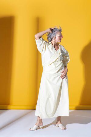 Fashionable woman. Fashionable mature beautiful woman wearing long white dress posing