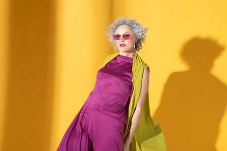 Suit and glasses. Curly grey-haired beautiful woman wearing pink suit and glasses