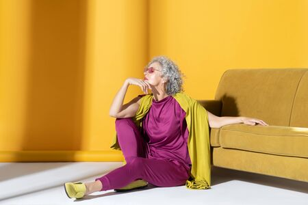 Sitting on floor. Curly mature stylish woman wearing pink suit sitting on the floor near sofa Stock fotó