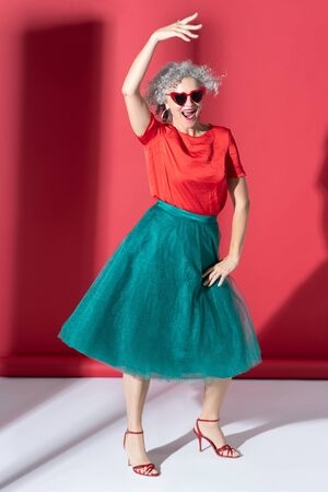 Emerald green skirt. Good-looking mature woman wearing emerald green skirt and high-heeled shoes Zdjęcie Seryjne