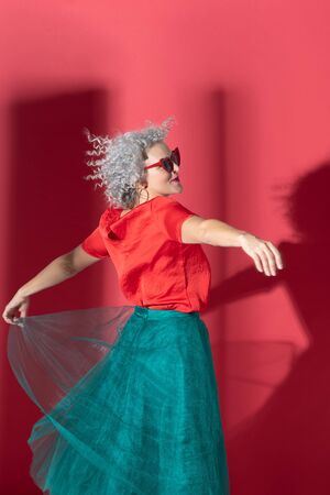 Dancing and spinning. Curly woman wearing emerald green skirt and red blouse dancing and spinning