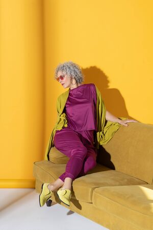 Woman on sofa. Curly mature woman wearing bright pink clothing and glasses sitting on sofa