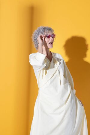 Curly woman. Curly mature woman wearing long baggy dress and bright sunglasses
