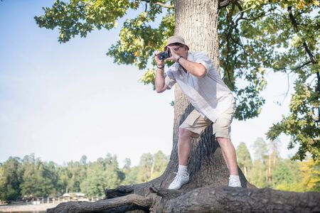 Man taking photo. Man wearing glasses taking photo of forest while standing near big tree Banque d'images