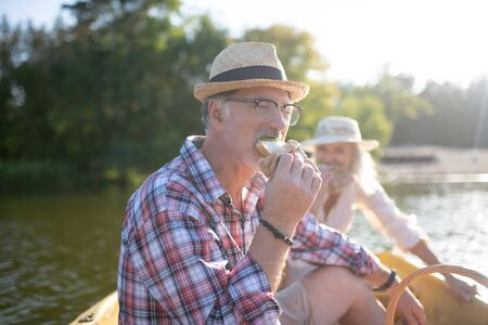 Biting yummy sandwich. Bearded grey-haired husband biting yummy sandwich sitting in boat with wife